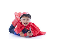 Child pretending to be a superhero with toy gun. And lying on the floor Royalty Free Stock Images