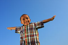 Child Pretending to Fly. Young child pretending to fly with blue sky background Royalty Free Stock Photography
