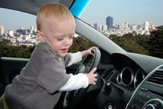 Child Pretends to Drive Car in Big City. Toddler stands up in parked car holding the steering wheel as he pretends to drive car with the San Francisco skyline in stock images
