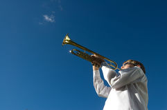 Child Prodigy. Young boy playing trumpet in white shirt against deep blue sky stock photography