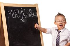 Child prodigy. Young boy playing a big scientist standing by blackboard with mathematical expectation formula written on it Stock Image