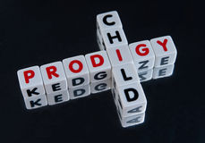 Child prodigy. Text ' child ' and ' prodigy ' inscribed on small cubes and arranged crossword style with common letter ' i ' dark background Royalty Free Stock Photos