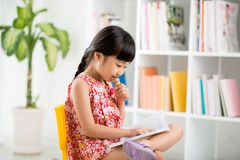 Child prodigy. Cute little girl eating ice-cream and reading a book Royalty Free Stock Image