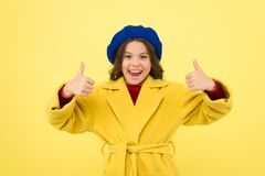 Child promoting something yellow background. Girl show thumbs up gesture. Advertising product. Look at this. Advertisement launching product. Advertisement royalty free stock image