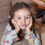 Child propped up hands head Stock Images
