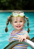 Child in protective goggles leaves pool. Royalty Free Stock Photography