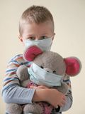 Child in protective mask. Child and toy in protective mask Stock Photos