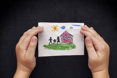 Child protects a drawn house with family Royalty Free Stock Photos