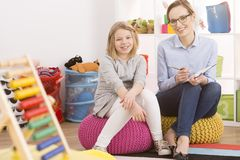 Child psychologist and little girl. Female child psychologist and little girl sitting on poufs in classes Stock Photography
