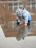 Child in a puddle. A little boy crouching down into a big puddle; with a reflection of a boy and a building Stock Photography