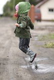 Child in a puddle. Child with rubber boots playinh in puddle after rain Royalty Free Stock Photo