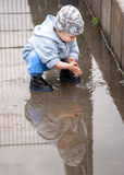 Child in a puddle. A toddler boy crouching down into a puddle playing with water; with a reflection of a boy Royalty Free Stock Image