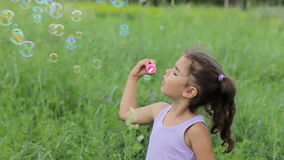Child puff soap bubbles. Girl inflate soap bubbles. Little curly girl blowing soap bubbles stock footage