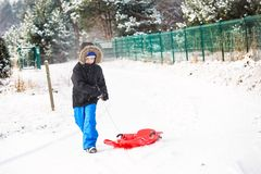 Child pulling red plastic sled. Royalty Free Stock Photos