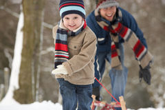 Child Pulling Sledge Through Winter Landscape Stock Photo