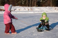 Child pulls another on snow scooter Royalty Free Stock Images