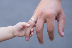 The child pulls the father`s finger. A ring on your finger Royalty Free Stock Photos
