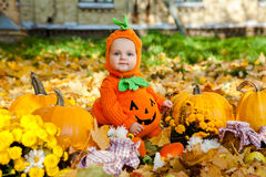 Child in pumpkin suit on background of autumn leaves Royalty Free Stock Images