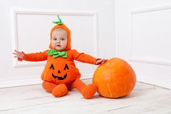 Child in pumpkin suit on white background with pumpkin Royalty Free Stock Photography
