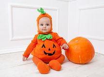 Child in pumpkin suit on white background with pumpkin Stock Photography