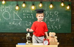 Child, pupil on smiling face near microscope. First former interested in studying, education. Wunderkind concept. Kid. Boy in graduate cap near microscope in stock photo