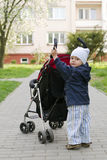 Child pushing stroller Royalty Free Stock Images