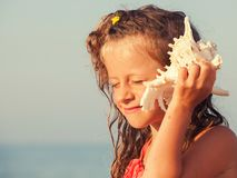 Child put the shell to her ear. Summer vacation. Girl on sea background royalty free stock photo