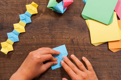 Child puts the modules. children`s creativity made of paper, origami crafts, handicrafts for children. Handmade. on wooden table Royalty Free Stock Photos