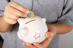 Child puts money. Child puts one euro in piggy bank Stock Images