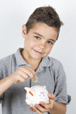 Child puts moneyin the piggy bank. Child puts  euro in piggy bank Royalty Free Stock Photography
