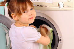 Child puts the towels in the washing machine Royalty Free Stock Images