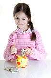 Child putting dollars in money box Stock Photo