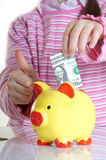 Child putting dollars in money box Stock Photography