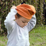 Child putting on hat Royalty Free Stock Image
