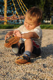 Child putting his shoes on Stock Photo