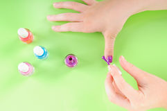 Child putting on nail polish. Young girl putting on own purple nail polish stock photography