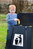 Child putting waste in bin. Young boy putting waste food scraps into a bin Stock Photo