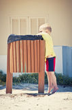 Child putting waste in the bin Stock Photos