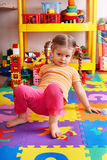 Child on puzzle with block  in playroom. Royalty Free Stock Images