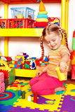 Child with puzzle and block in playroom. Royalty Free Stock Images