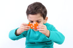 Child with puzzle. Child with orange puzzle isolated on white royalty free stock image