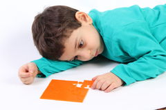 Child with puzzle. Child with orange puzzle isolated on white royalty free stock photography