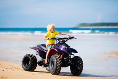 Child on quad bike at beach. All-terrain vehicle. Little boy riding quad bike on tropical beach. Cute blond curly child on quadricycle. All-terrain vehicle ride Stock Photos
