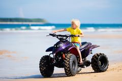 Child on quad bike at beach. All-terrain vehicle. Little boy riding quad bike on tropical beach. Cute blond curly child on quadricycle. All-terrain vehicle ride Stock Images