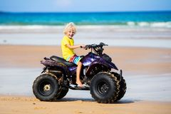 Child on quad bike at beach. All-terrain vehicle. Little boy riding quad bike on tropical beach. Cute blond curly child on quadricycle. All-terrain vehicle ride Royalty Free Stock Photos