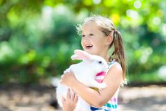 Child with rabbit. Easter bunny. Kids and pets. Child playing with white rabbit. Little girl feeding and petting white bunny. Easter celebration. Egg hunt with stock photos