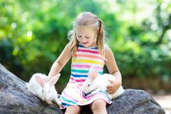 Child with rabbit. Easter bunny. Kids and pets. Child playing with rabbit. Little girl feeding white bunny. Easter celebration. Egg hunt with kid and pet animal Stock Photography