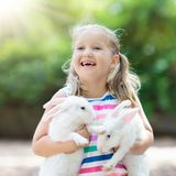 Child with rabbit. Easter bunny. Kids and pets. stock photo