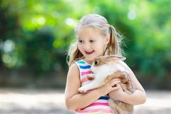 Child with rabbit. Easter bunny. Kids and pets. Child playing with white rabbit. Little girl feeding and petting white bunny. Easter celebration. Egg hunt with Stock Photography