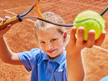 Child with racket and ball on  tennis court Royalty Free Stock Image